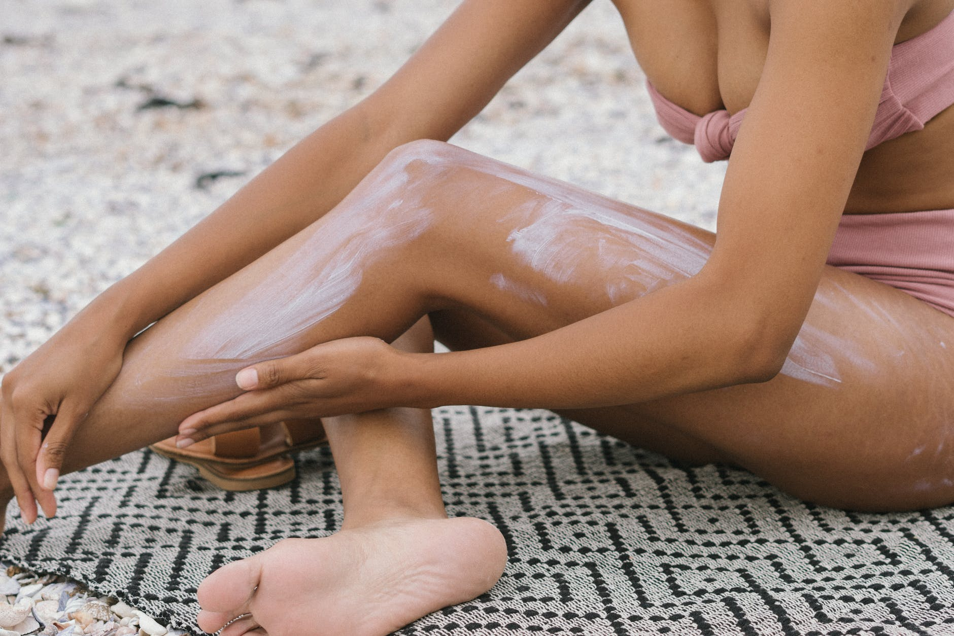 woman seated on textile applying suncsreen