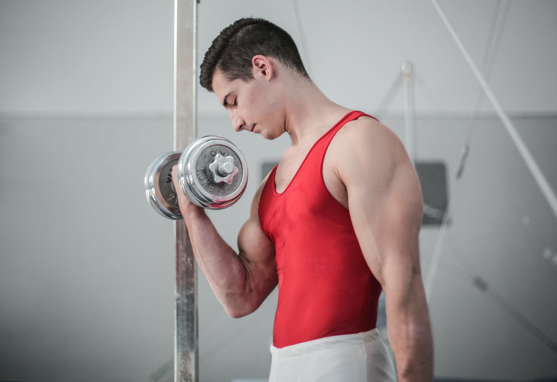 photo of male gymnast doing dumbbell bicep curls