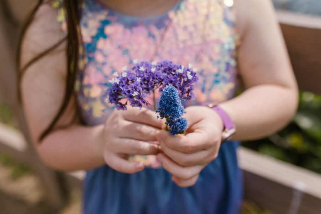 girl in blue and pink floral tank top holding purple flower